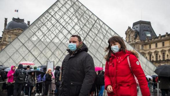 Two people wear a mask outside the Louvre this Monday (EFE)